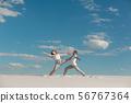 Romantic couple dancing in sand desert at blue sky 56767364