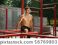 Young muscular man while doing his workout outside at playground 56769803
