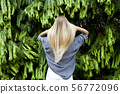 Beautiful young woman standing in the forest 56772096