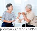 Two Asian elderly women hook each others little 56774959