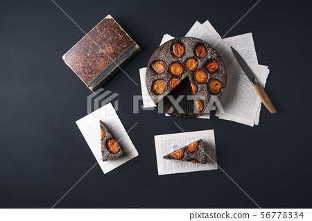 Plums chocolate cake and slices on book pages 56778334