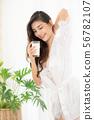Beautiful women  holding a glass of milk. 56782107