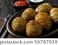 Hasselback potatoes baked with garlic and herbs  56787939
