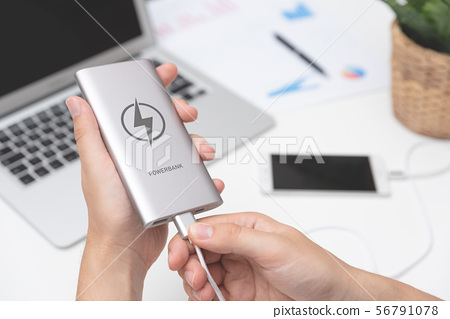 Man connecting USB charger to smart phone 56791078