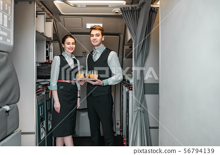 Smiling flight attendant with pilot posing for camera 56794139