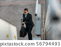Businessman lifting up on plane ladder in airport 56794493