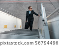 Businessman going up on plane ladder in airport 56794496