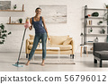 Young female having fun during household chores stock photo 56796012