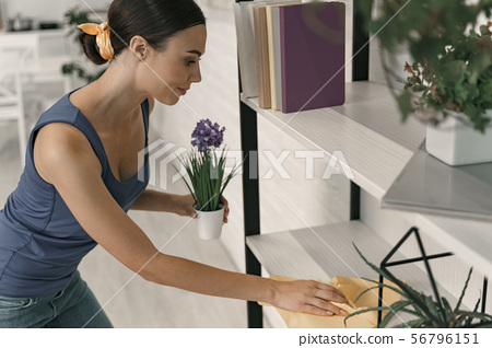 Smiling woman enjoying cleaning house stock photo 56796151