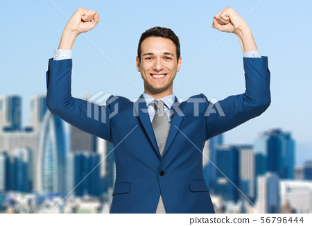 Businessman smiling and raising his fist in the 56796444