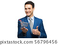 Smiling businessman holding a mini shopping cart 56796456