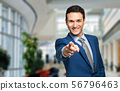 Portrait of young businessman pointing finger at 56796463