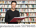 Guy reading a book in a library 56796485