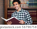 Handsome man stands by bookshelves 56796758