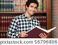 Handsome man stands by bookshelves 56796806