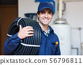Portrait of a smiling worker carrying corrugated 56796811