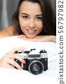 Beautiful young woman holding retro camera and smiling 56797982