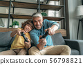 Mature father with little kid playing in video games 56798821
