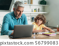 Father using laptop while son making homework 56799083