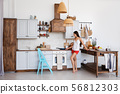 Lifestyle photo of cute girl standing by the stove 56812303