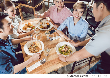 Male waiter serving food on table 56815876