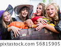 Women wearing witch costumes while posing together at Halloween 56815905