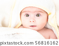 Adorable baby girl after bath wrapped in towel. Looking up with big brown eyes. Copy space 56816162