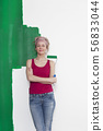 Woman with paint roller in front of wall 56833044