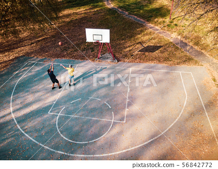 Father and son playing basketball in the park 56842772
