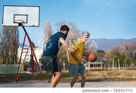 Senior man playing basketball with his son in a 56842773