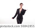 Fashion model looking amazed wearing black jacket in studio over white background 56842855