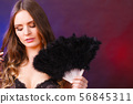 Woman holding carnival feather fan in hand. 56845311