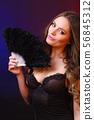 Woman holding carnival feather fan in hand. 56845312