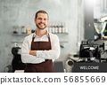 Bearded man wear brown apron looking at camera. 56855669