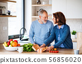 A portrait of senior couple indoors at home, unpacking shopping. 56856020