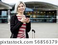 Smiling Female Traveler Using Smart Phone Outside Train Station 56856379