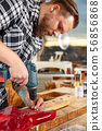 Portrait of craftsman working in workshop with guitar 56856868