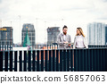 Two young business people with tablet standing on a terrace outside office, working. 56857063