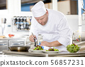 Chef prepares steak dish at gourmet restaurant 56857231