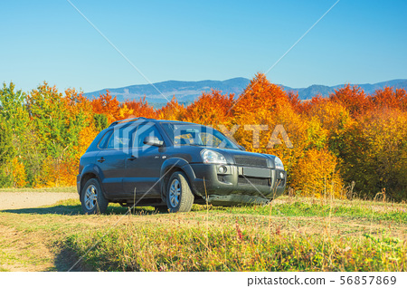 suv on the gravel country road side in mountains 56857869