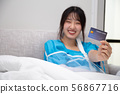 Asian woman holding insurance credit cards  56867716