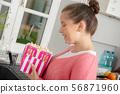 young teenage girl with pink sweater eating 56871960