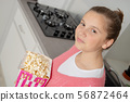 young teenage girl with pink sweater eating 56872464