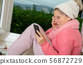 young teen girl with a pink sweater and winter cap 56872729