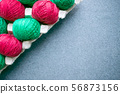 Balls of colored red and green yarn in a paper egg 56873156