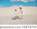 Handsome guy makes the girl a proposal for marriage, bending his knee, standing on the sand in the 56878704
