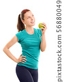 Smiling young girl in fitness clothes with apple 56880049