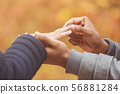 Man putting engagement silver ring on woman hand 56881284