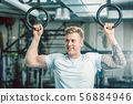 Handsome young man with strong arms hanging on gymnastic rings at the gym 56884946