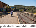 A young woman wearing a cowboy hat takes a photograph of the Extremadura railway track near 56886408